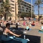 Prop d'un centenar de persones gaudeixen d'una classe grupal de ioga al passeig Marítim de Badalona